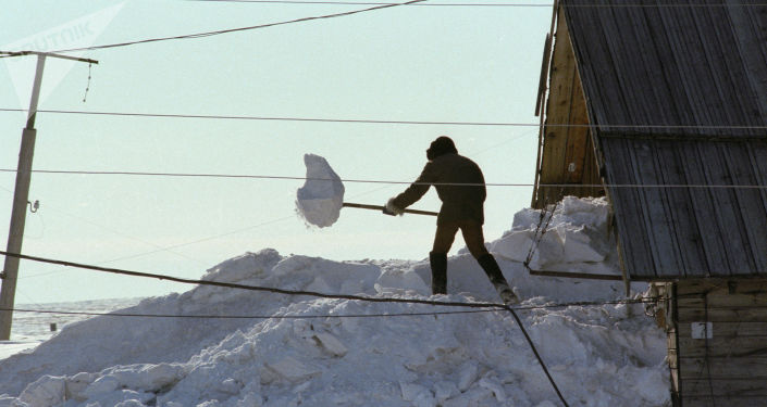 Abitante dell'isola spala la neve per uscire di casa (1980)