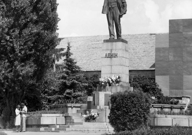 Una coppia di innamorati sotto la statua di Lenin