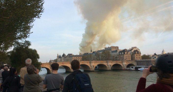 Parigini e turisti fotografano da lontano l'incendio