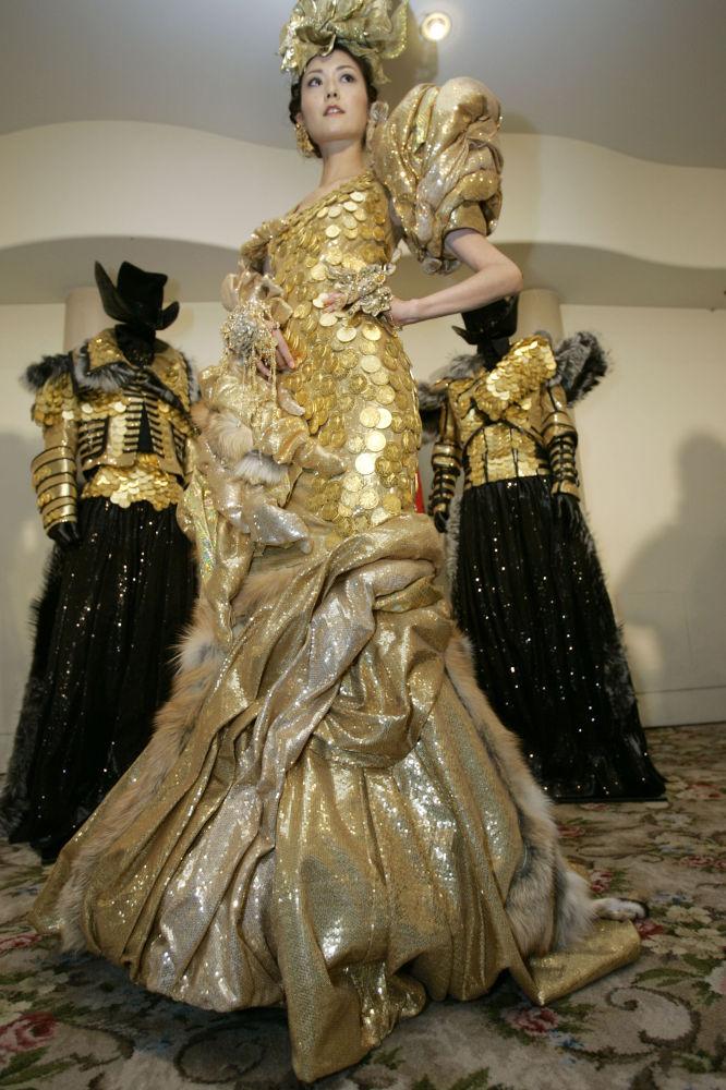 Una modella sfila con un'abito da sera composto da 325 monete d'oro del valore di 270 mila dollari realizzato dall'orafa Ginza Tanaka.