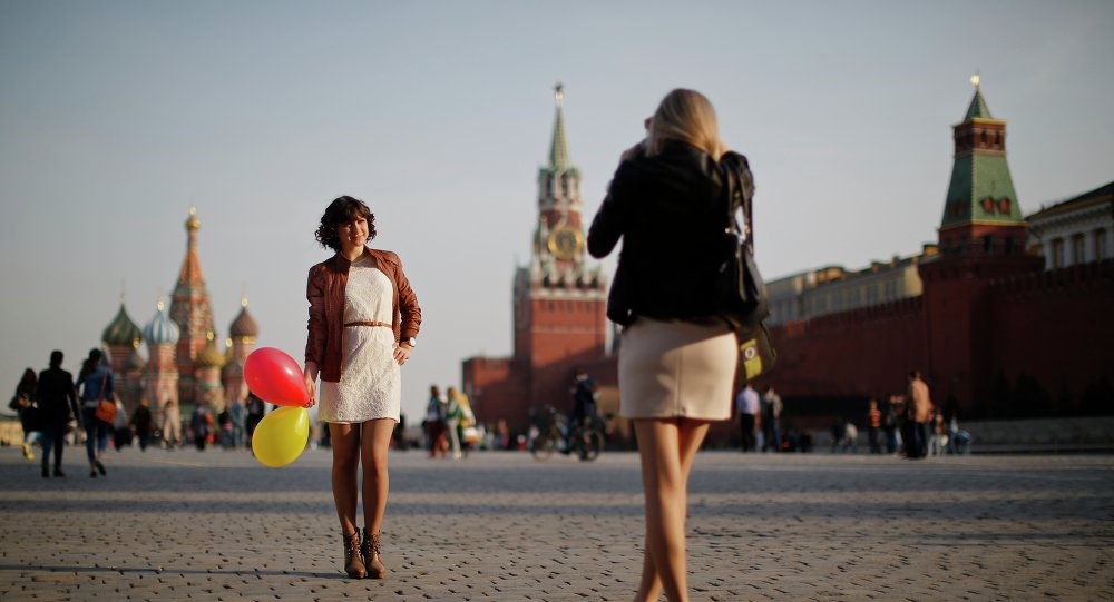 A young woman takes a pictures of her friend as the sun sets in Red Square in Moscow, Russia, Tuesday, March 25, 2014