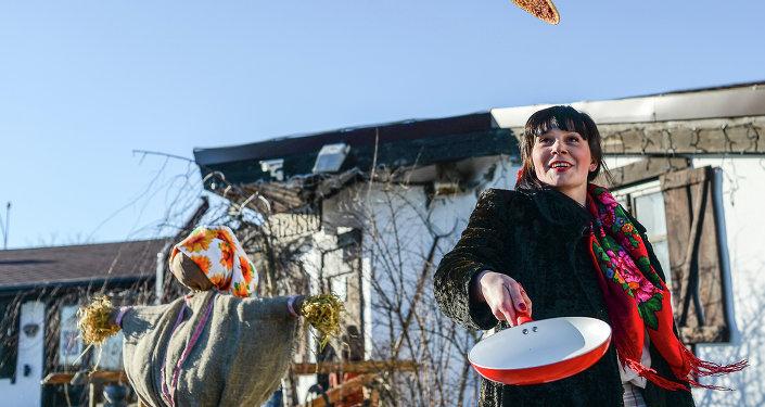 Una donna nei tradizionali costumi russi prepara il tipico dolce bliny per la festa di Maslenitsa, che anticipa il periodo pre pasquale