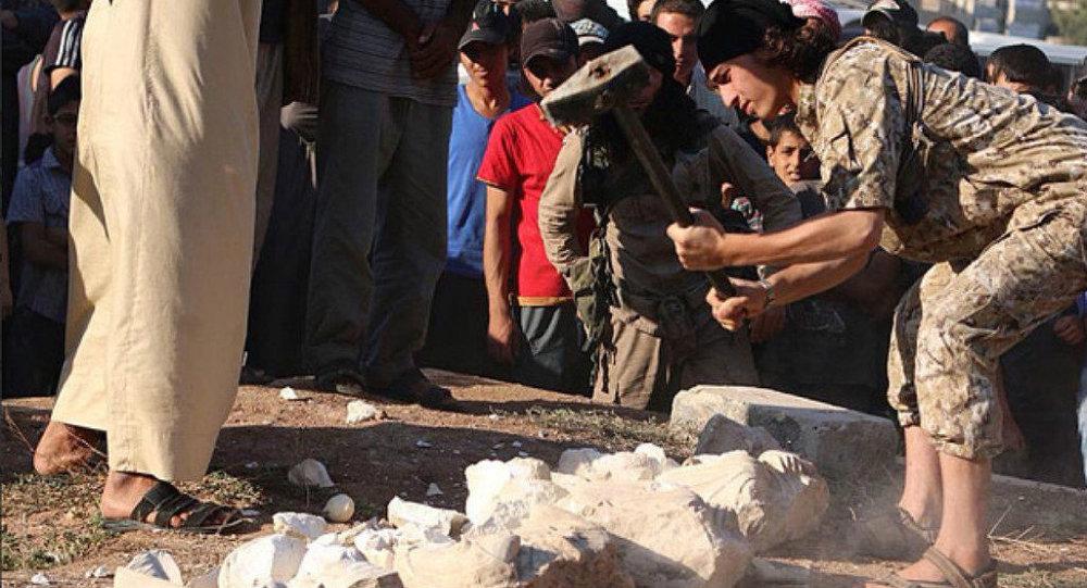 Un combattente dell'ISIS distrugge una statua storica di fronte a una folla, Palmira