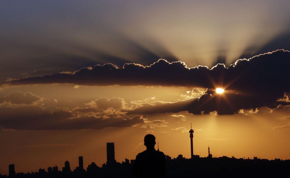 Un uomo guarda il tramonto a Johannesburg.