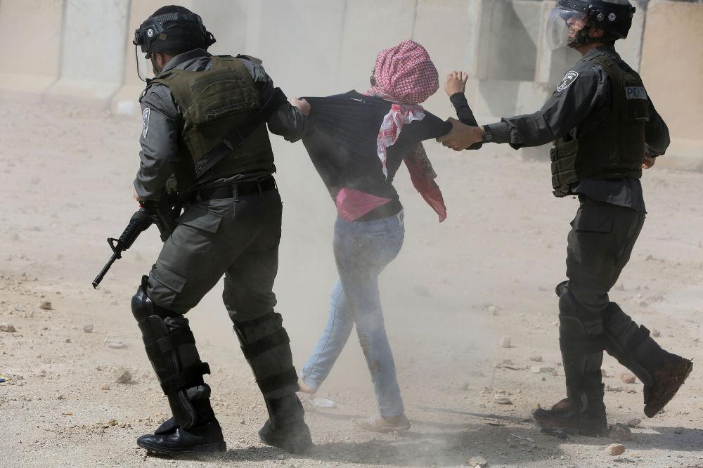 I soldati israeliani arrestanto una studentessa palestinese.
