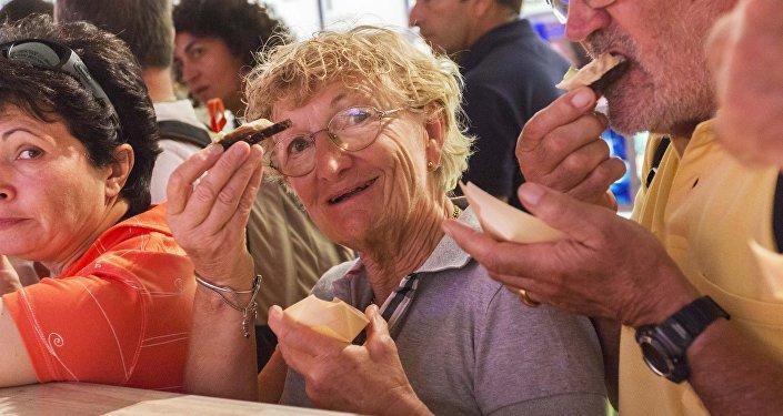 Visitatori entusiasti degustano il caviale al padiglione russo