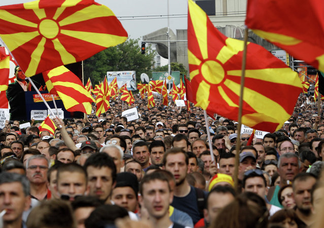 People wave national flags during a protest in front of the Government building in Skopje, Macedonia.