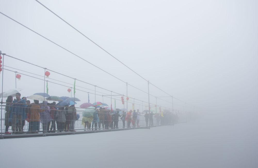 I turisti cinesi sul ponte di vetro sospeso nelle montagne della Cina.