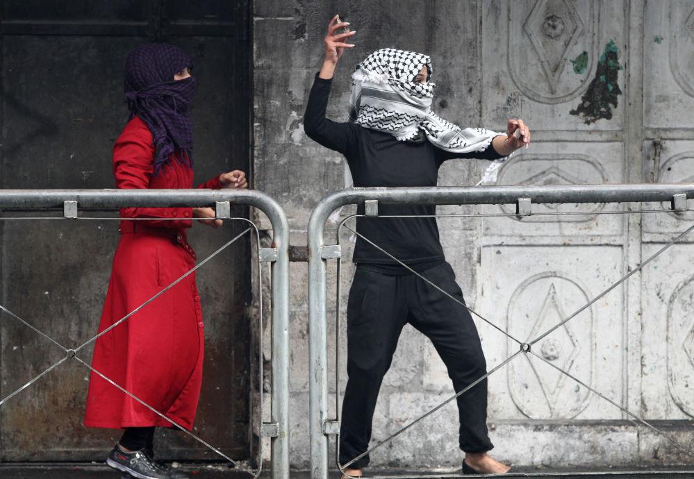 Due donne palestinese gettano sassi contro militari israeliani durante gli scontri in Cisgiordania.