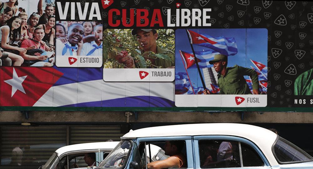 Cuba, scritte che inneggiano alla rivoluzione mentre passa un'auto americana