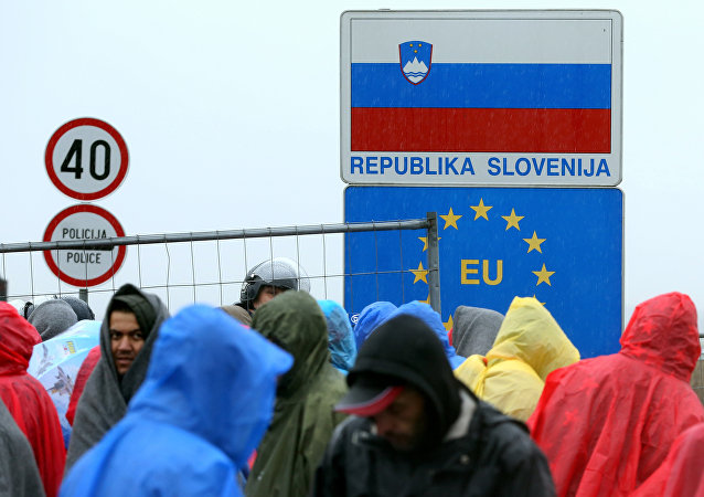 Migrants and refugees wait in the rain as they wait to enter Slovenia, at the Croatian-Slovenian border in Trnovec, on October 19, 2015.