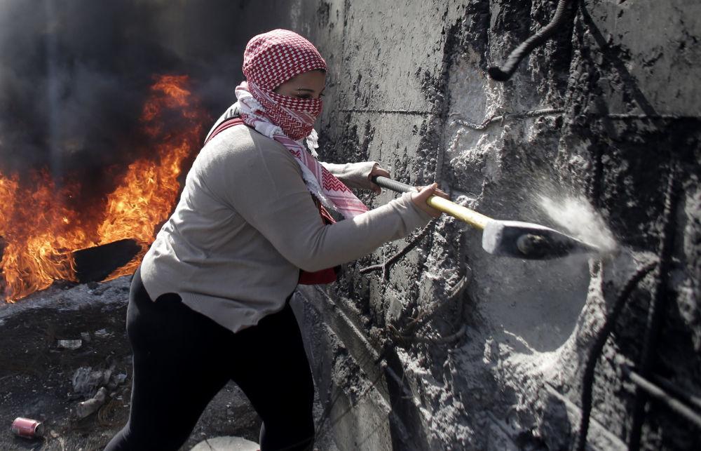 Una donna palestinese con un'ascia distrugge la barriera in Gerusalemme Est.