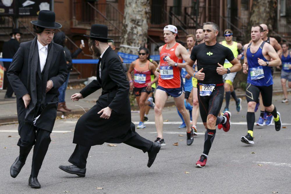 Due ebrei cercano di attraversare la strada davanti ai partecipanti nella maratona a Brooklyn.