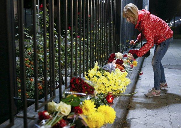 Una donna posa dei fiori in memoria delle vittime dell'attentato all'aereo russo nel SINAI