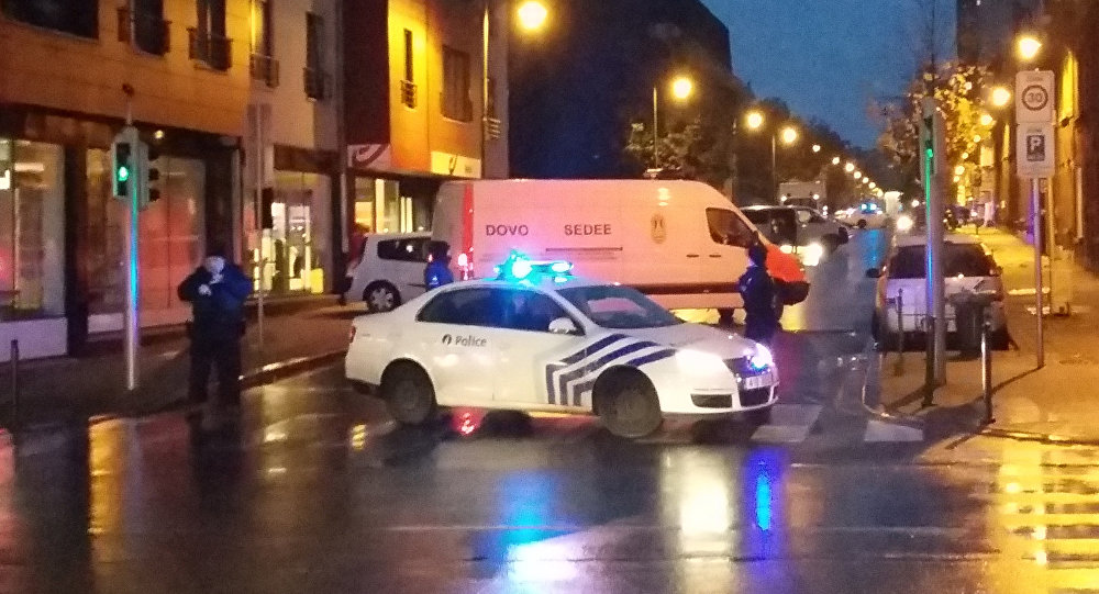 A photo taken on November 14, 2015 with a mobile phone shows a van of the Belgian bomb disposal unit SEDEE as police block a street during a police raid possibly in connection with the November 13 deadly attacks in Paris, in Brussels' Molenbeek district