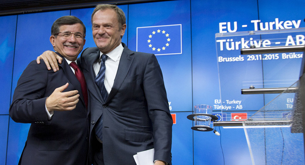 Il presidente del Consiglio Europeo Donald Tusk abbraccia il primo ministro turco Ahmet Davutoglu dopo il vertice UE-Turchia a Bruxelles il 29 Novembre, 2015.