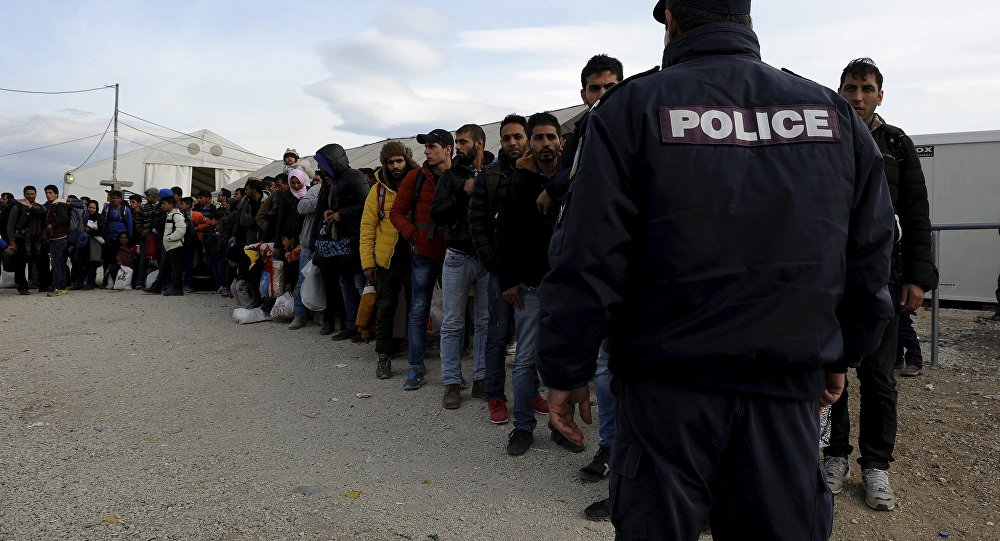 Refugees and migrants line up inside a camp, as they wait to cross Greece's border with Macedonia near the Greek village of Idomeni, November 10, 2015