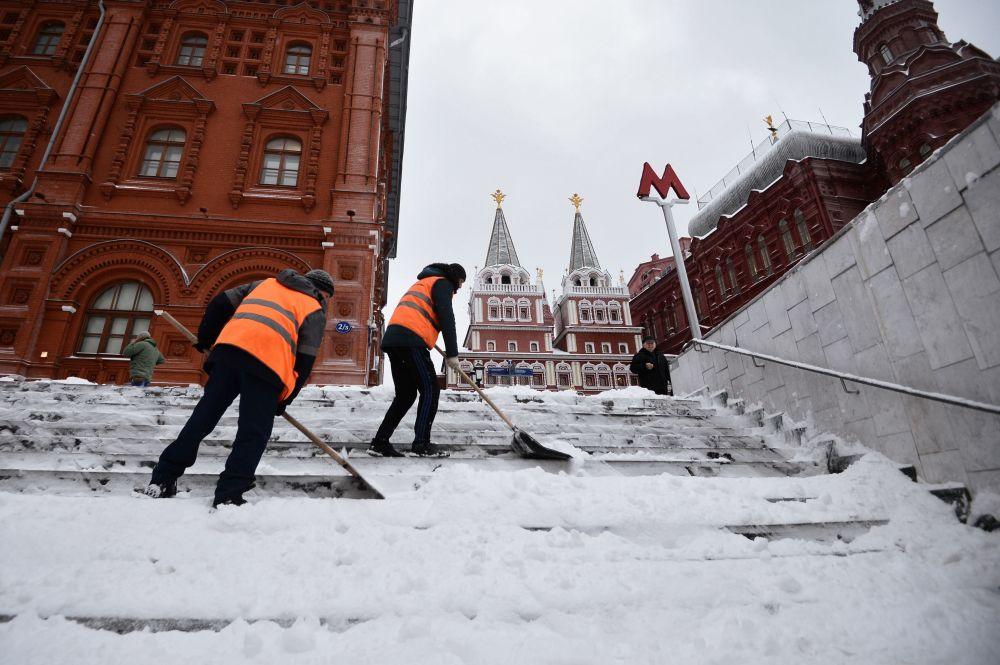 Gli operai del servizio pubblico rimuovono la neve dalle scale di accesso alla metropolitana.