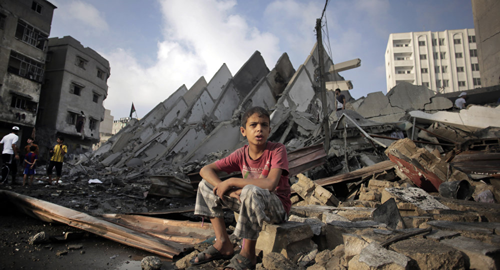 A Palestinian boy sits next to the destroyed 15-story Basha Tower following early morning Israeli airstrikes in Gaza City, Tuesday, Aug. 26, 2014.