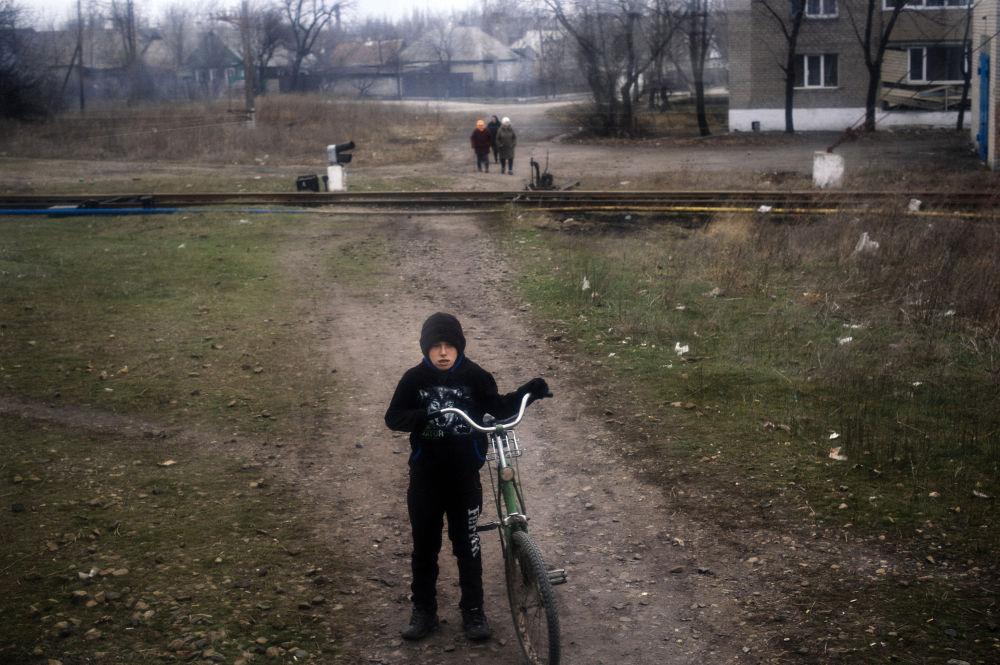 Un bambino aspetta il passaggio del treno.