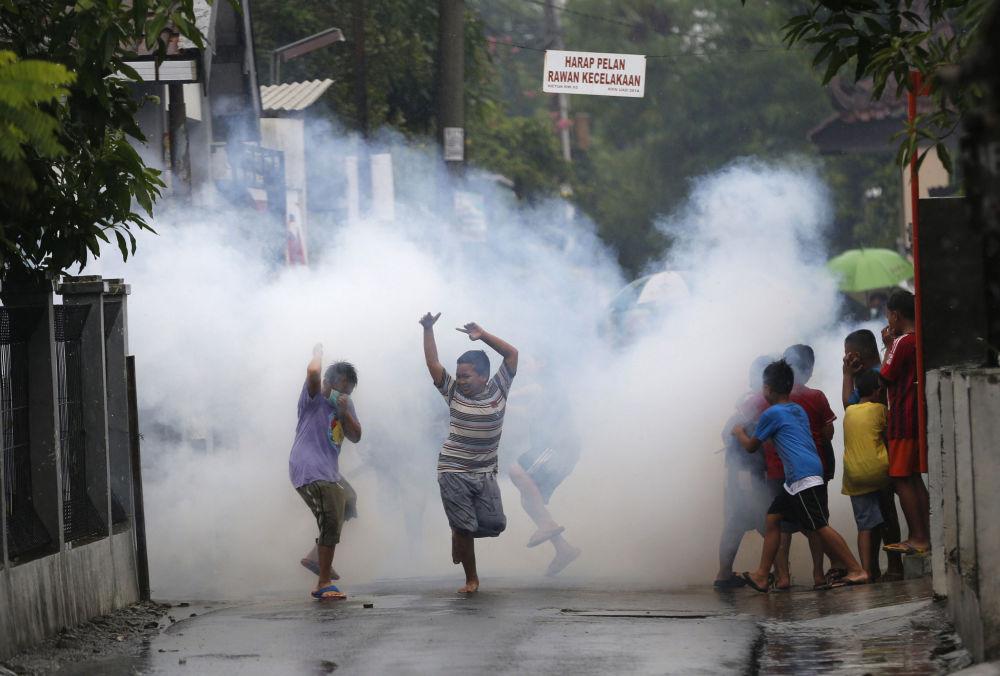 Bambini giocano mentre si diffonde l'agente chimico contro mosquiti, Indonesia.
