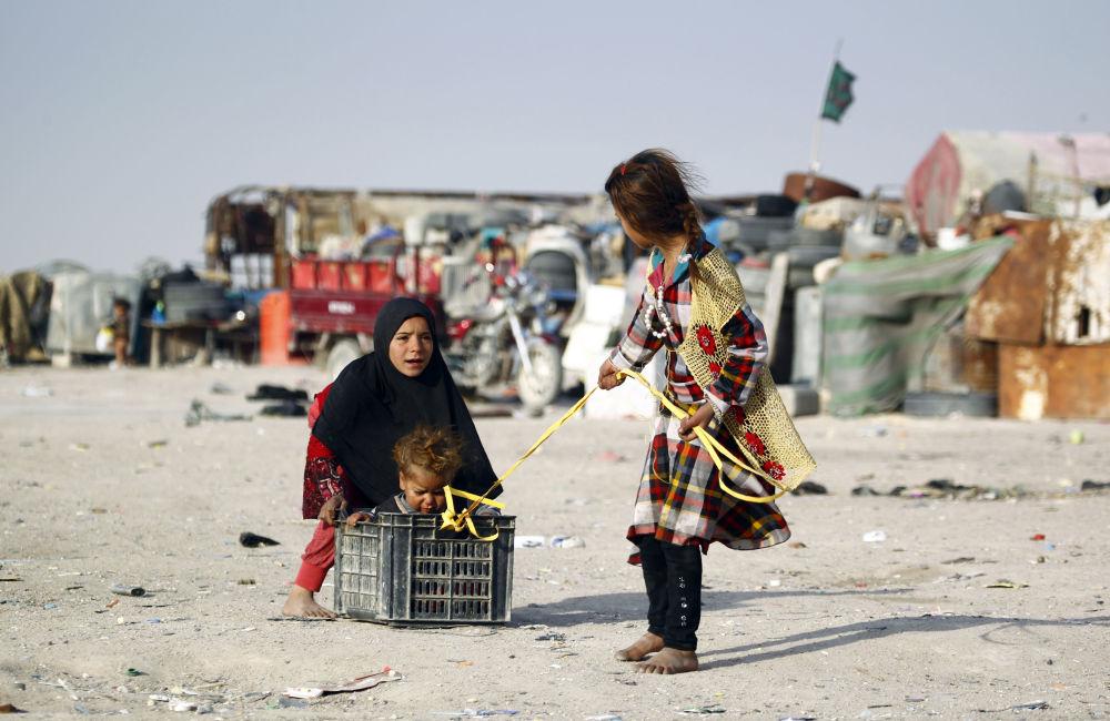 Bambini di una famiglia povera irachena giocano alle strade della città di Najaf.