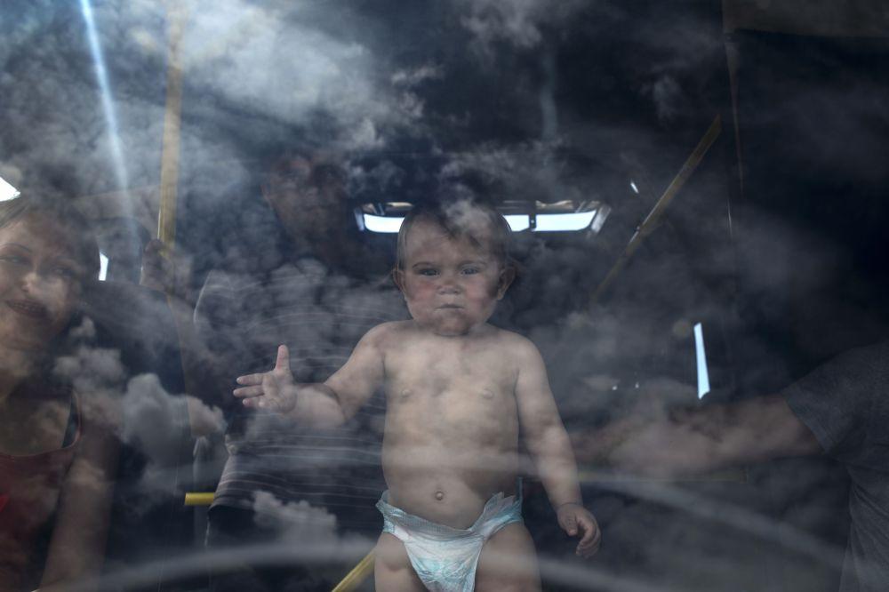 Un bambino su un autobus destinato al trasporto dei profughi a Lugansk.