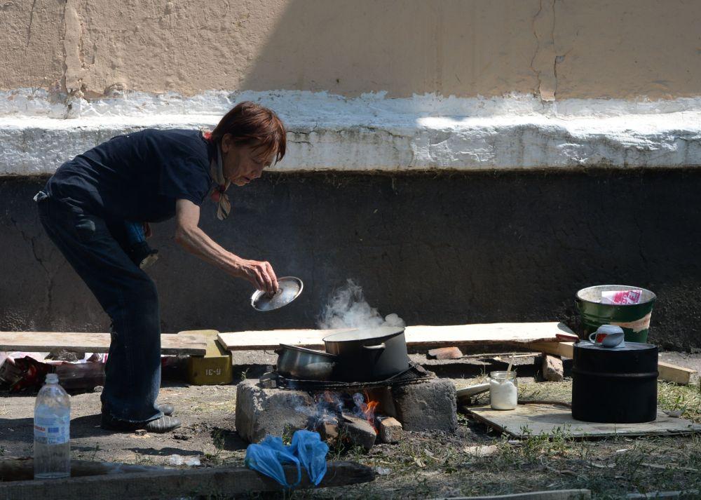 Una donna di Schaktersk prepara da mangiare sul fuoco vivo nei pressi della sua casa.