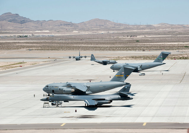 Several C-17 Globemaster IIIs, C-130 Hercules and a B-1 Lancer park on the flightline May 31, 2013, at Nellis Air Force Base, Nev