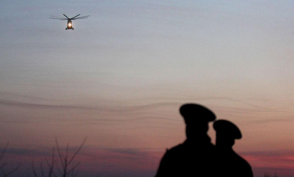 Poliziotti russi osservano da lontano, da terra, il volo dell'elicottero su cui sono trasportate le bare.