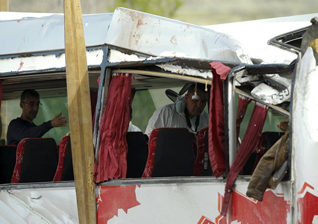 Forensic experts inspect the wreckage of a bus after a traffic accident in Freginals, Spain, March 20, 2016.