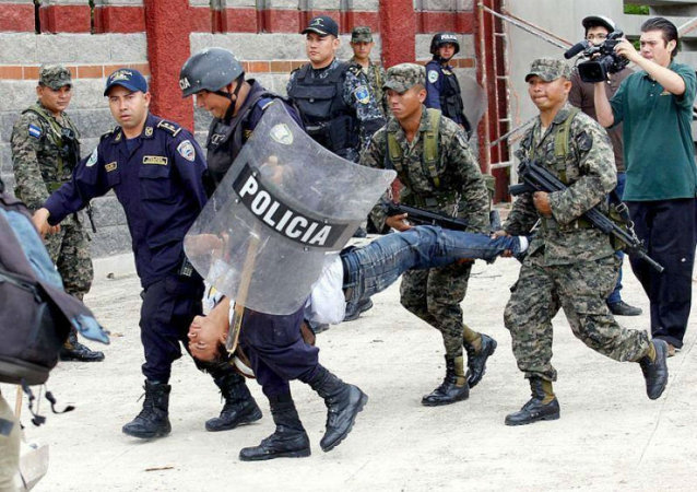 Police and military personnel carry away an injured protester in Tegucigalpa, Honduras.