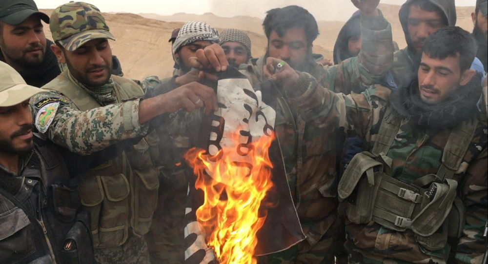Soldati siriani bruciano bandiera del Daesh a Palmira