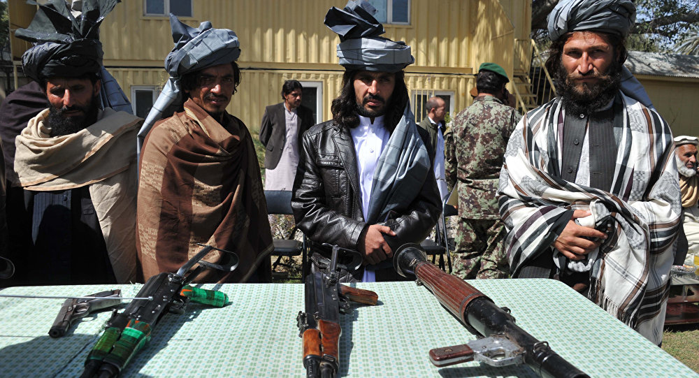 Former Taliban fighters look on as they stand alongside their weapons in Jalalabad, the capital of Nangarhar province on March 19, 2014