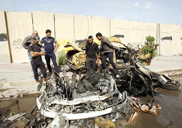Iraqi men inspect the site of car bomb attack in Baghdad, Iraq (File)
