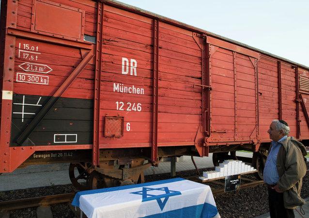 Un israeliano sosta di fronte ad uno dei vagoni usati per trasportare gli ebrei nei lager .