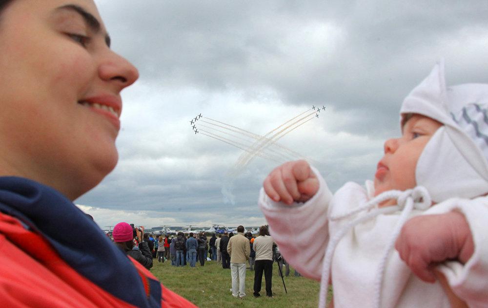 Una mamma tiene in braccio la sua bambina mentre sullo sfondo è in corso l'esibizione delle Frecce Tricolori.