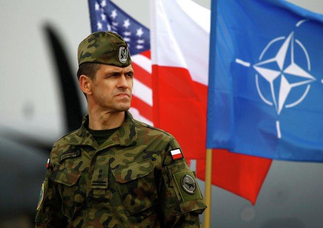 Soldato polacco di fronte alle bandiere di USA, Polonia e NATO