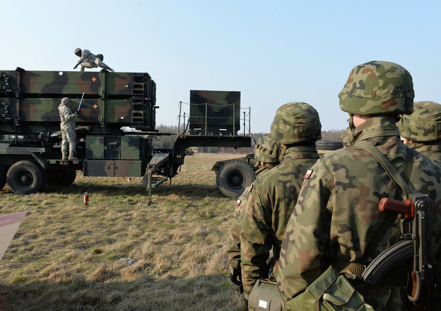 Polish soldiers watch as US troops from the 5th Battalion of the 7th Air Defense Regiment emplace a launching station of the Patriot air and missile defence system at a test range in Sochaczew, Poland, on March 21, 2015