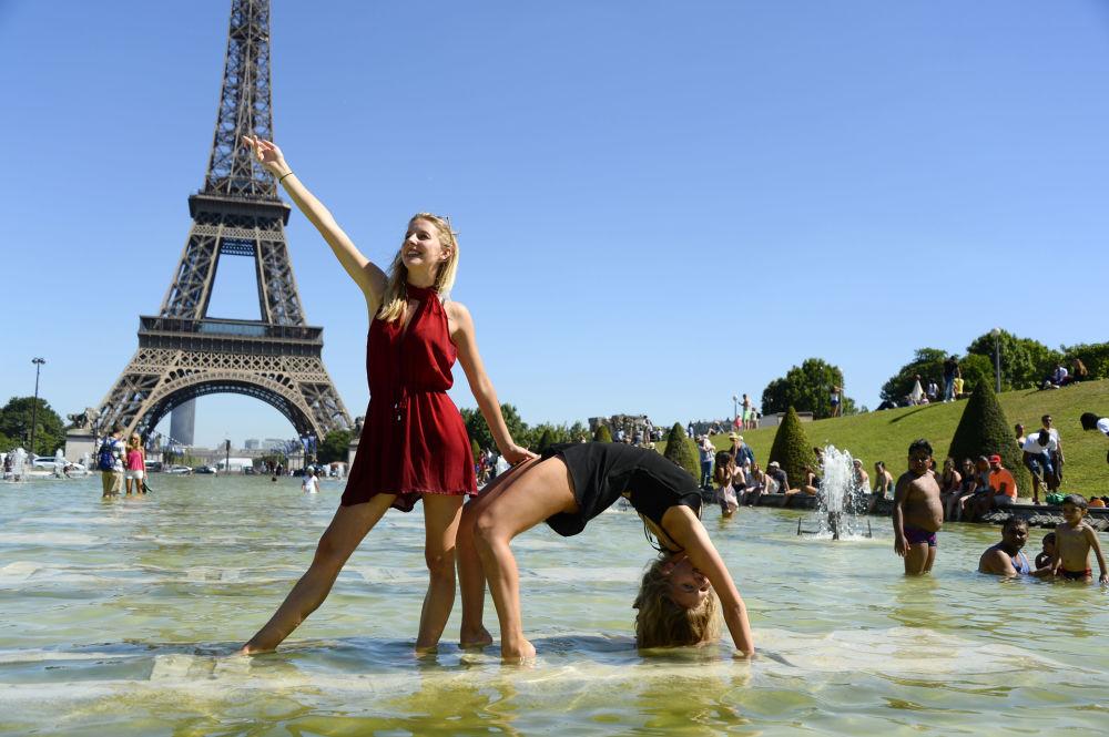 Due ragazze posano per una foto di fronte alla Torre Eiffel di Parigi.