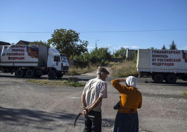 Due abitanti del Donbass guardano i camion che portano gli aiuti umanitari