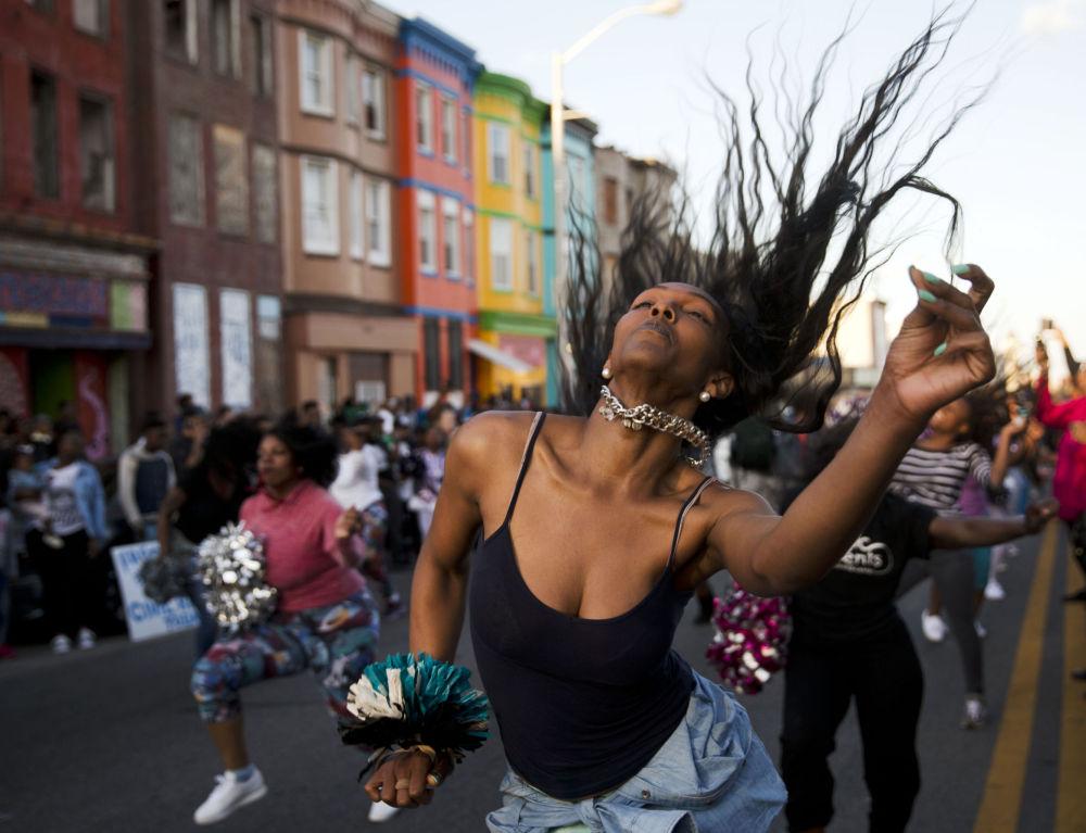 Una ragazza balla per strada a Baltimore durante le proteste.