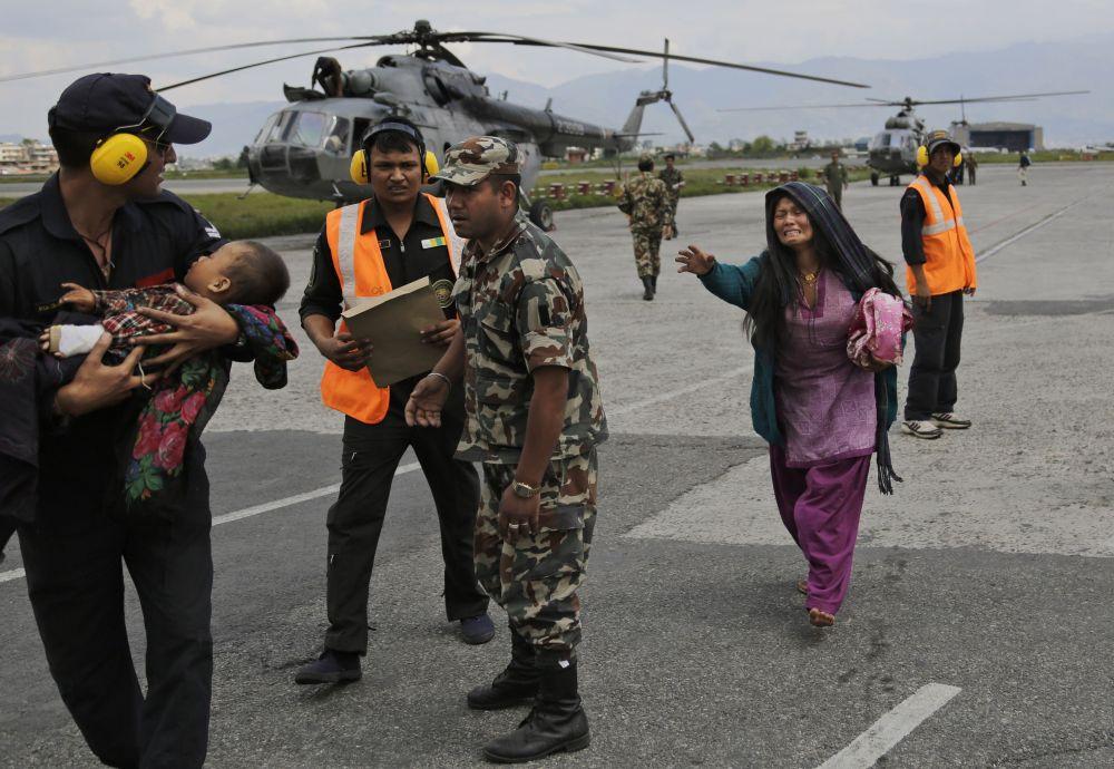 Un bambino viene portato in salvo su un elicottero in Nepal.