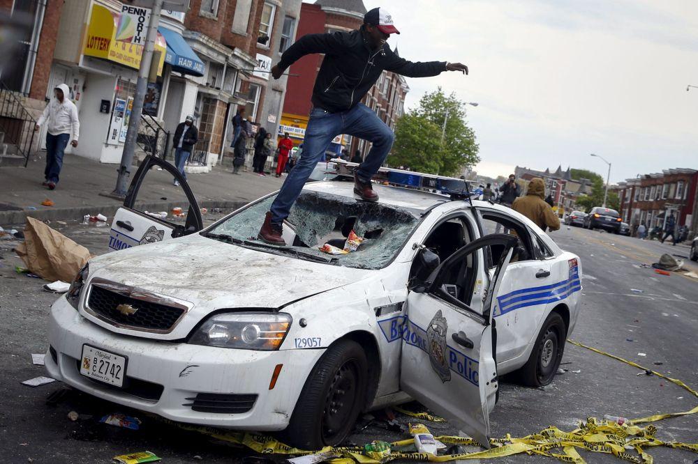Baltimore, un manifestante sale sopra un'auto della polizia.