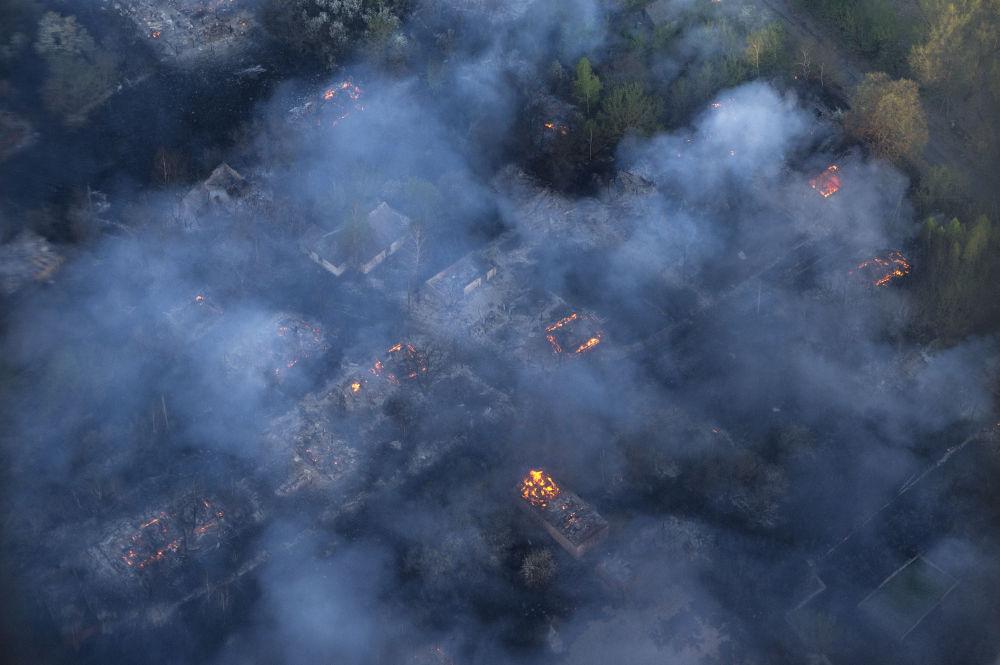 Il fuoco avvolge un villaggio abbandonato nei pressi di Chernobyl in Ucraina.