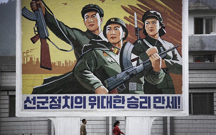 Corea del Nord, la gente passa sotto il poster Evviva la vittoria della politica dell'esercito prima di tutto nel centro della città di Wonsan.