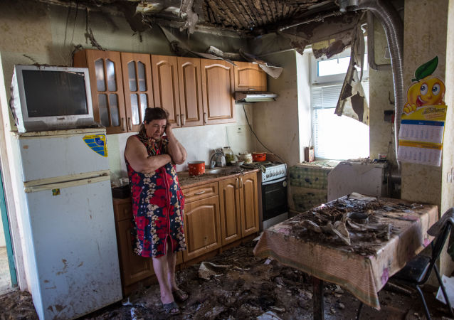 Una donna osserva disperata il suo appartamento distrutto dalle bombe a Donetsk.