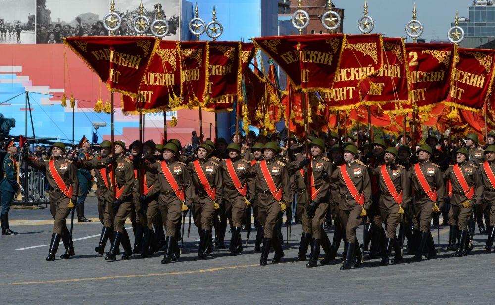 Soldati con gli emblemi delle divisioni d'appartenenza sfilano sulla Piazza Rossa.
