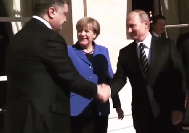 Putin e Poroshenko si stringono la mano.