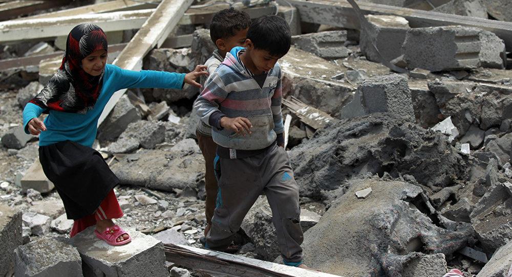 Bambini camminano sulla mecerie di una casa in Yemen
